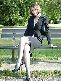 Cute brunette outdoors wearing stockings and black high..