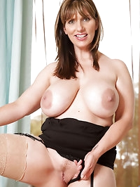 Cougar babe pinches her huge boobs on the couch and slides..