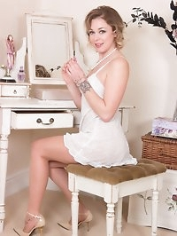 Lucy is at her dressing table when you catch her, getting..