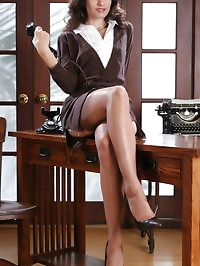 Beautiful lady in business suit and stockings poses in the..