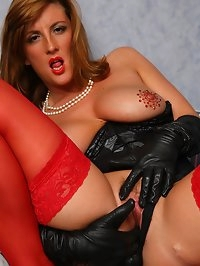 Jenny plays on the bed in her basque, stockings and gloves