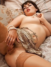 Hairy mature babe Angelina Dee naked on her bed.