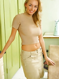 Busty blonde in a sexy brown skirt, top, boots and tan..