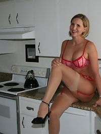 Desirae in kitchen with red lingerie and garters