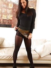 Stunning brunette in gold shiny miniskirt with opaque..